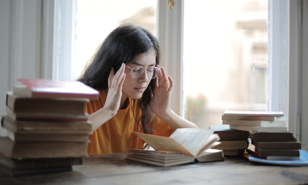 girl sitting at a desk surrounded by books