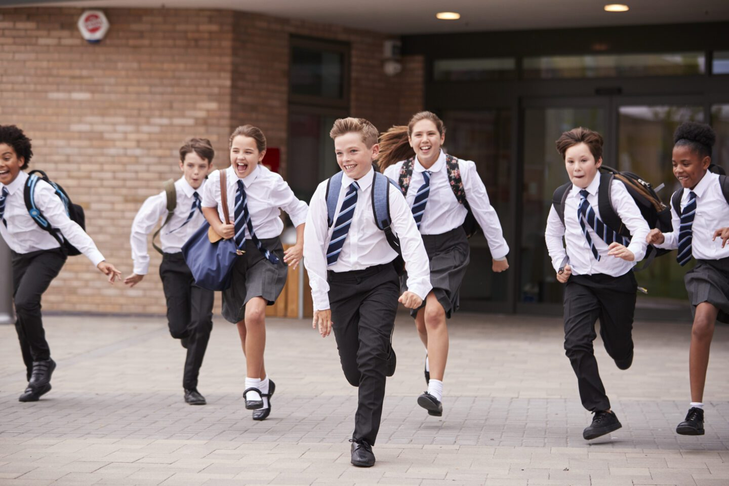 Group Of excited School Students Wearing Uniform Running Out Of School Buildings Towards Camera