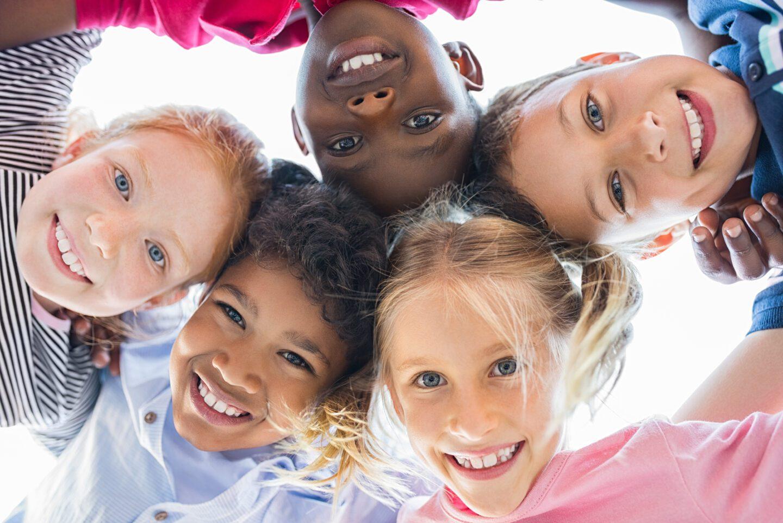 closeup of happy children hugging in a circle