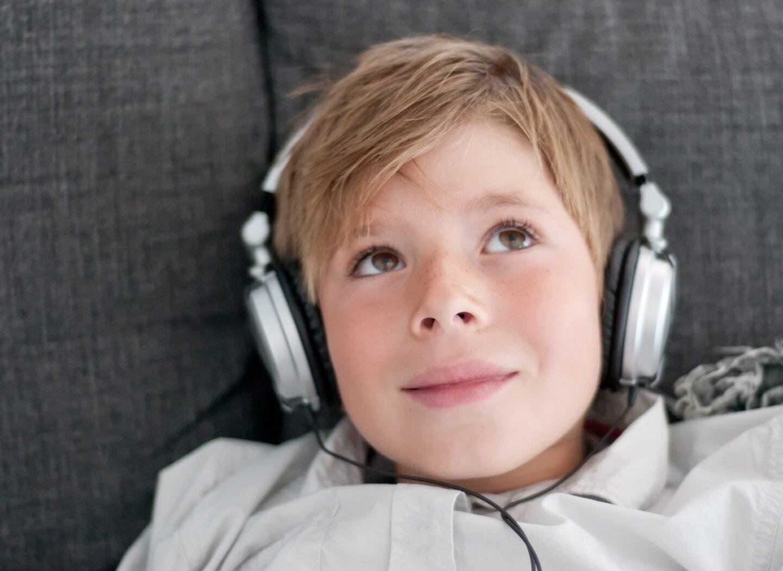 young boy wearing headphones listening to an audiobook