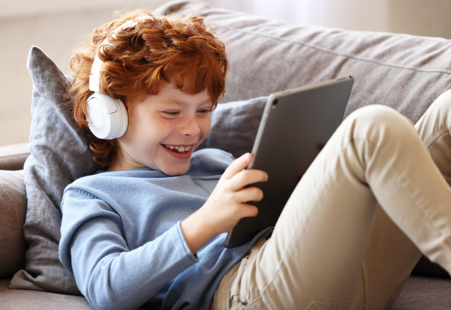 little boy sitting on a sofa smiling at his iPad as he listens to a podcast
