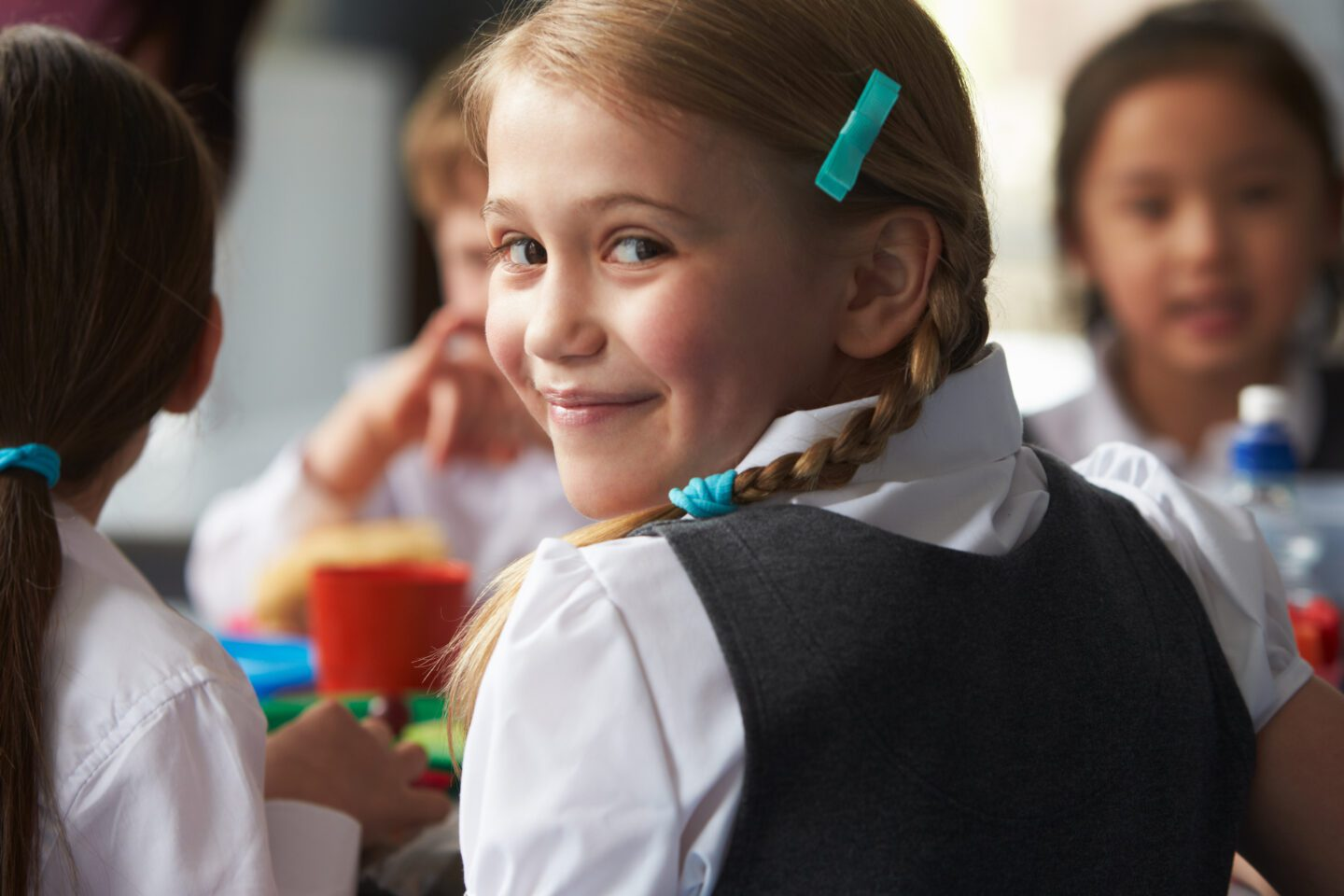 young girl smiling and looking over her shoulder into the camera